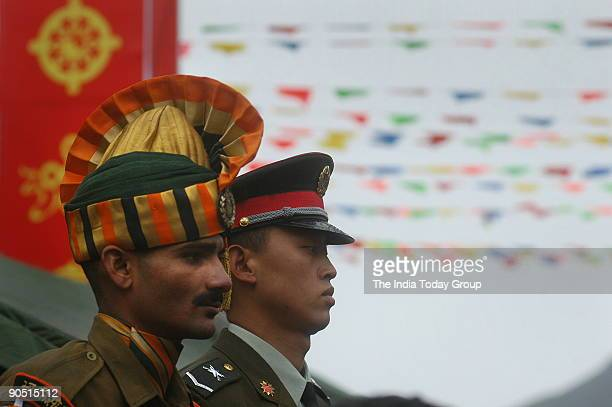 An Indian soldier and a Chinese soldier both in ceremonial dress stand side by side on the border at Nathu La on the day of the opening Trade between...
