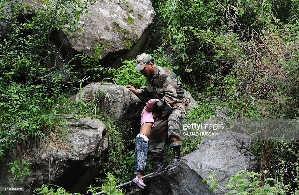 An Indian soldier assists a child as stranded Indian pilgrims coming from Badrinath make their way down a mountain at Govindghat following flash floods in northern Uttarkhand state on June 30, 2013. Some 3,000 tourists and pilgrims remain missing in India's flood-ravaged north two weeks after the tragedy, but it is unclear how many of those have been killed, a top state official said June 30.
