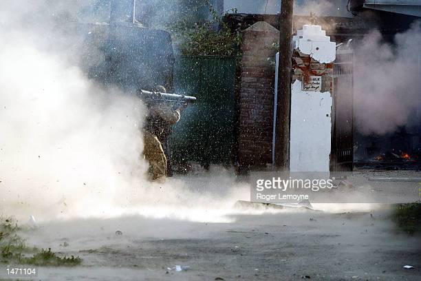 An Indian soldier fires a grenade into a home near a polling station and army camp where two militants went on a shooting spree killing a policeman...