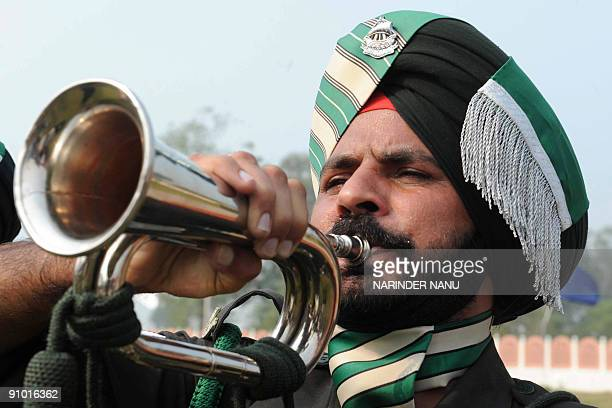 An Indian soldier from the 54th Infantry Brigade blows a bugle at the Dograi War Memorial at Khasa Military Station some 15 km from Amritsar on...