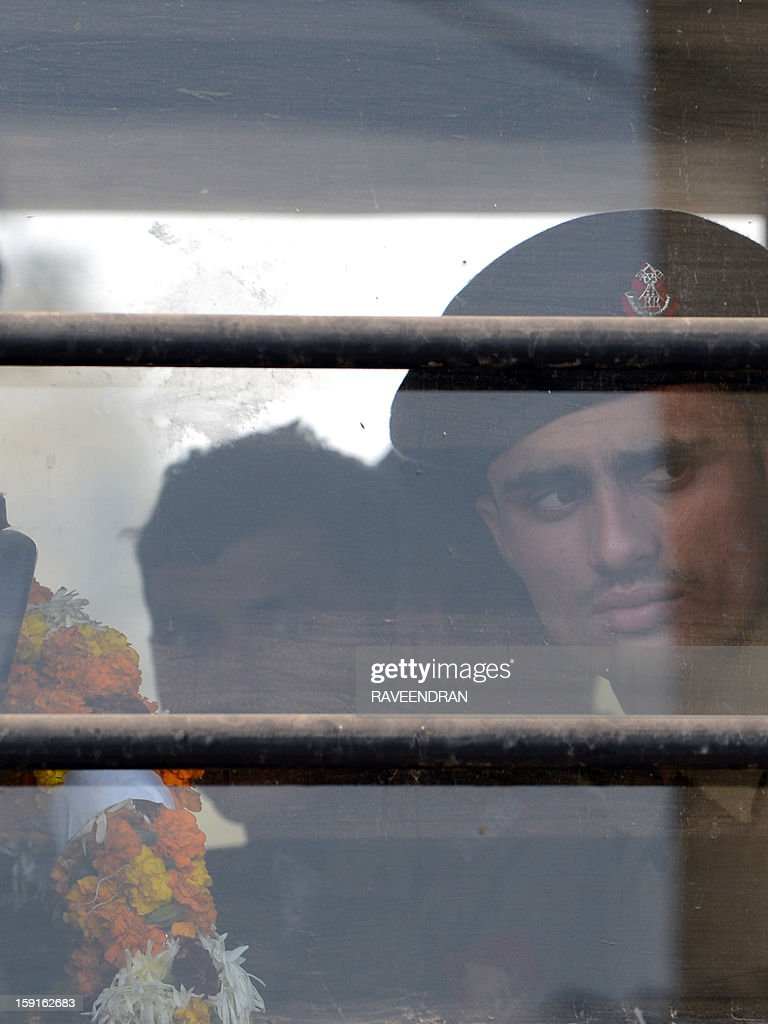 An Indian soldier holding a wreath looks on from inside a military truck as he waits for the arrival of the bodies of two comrades, allegedly killed by Pakistani soldiers in a cross-border skirmish in the disputed Kashmir region, at the New Delhi Air Force Station on January 9, 2012. India delivered a dressing-down to Islamabad's envoy to Delhi as it accused Pakistan's army of beheading one of two soldiers killed in Kashmir, but both sides warned against inflaming tensions. AFP PHOTO/RAVEENDRAN