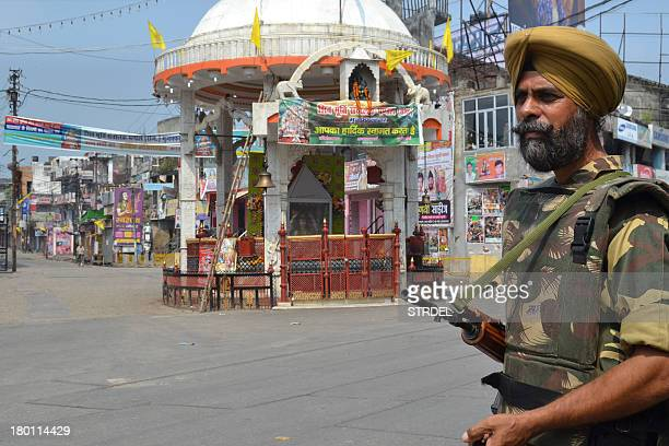 An Indian soldier keeps watch on a deserted street following communal riots between Muslims and Hindus in Muzaffarnagar India's Uttar Pradesh state...