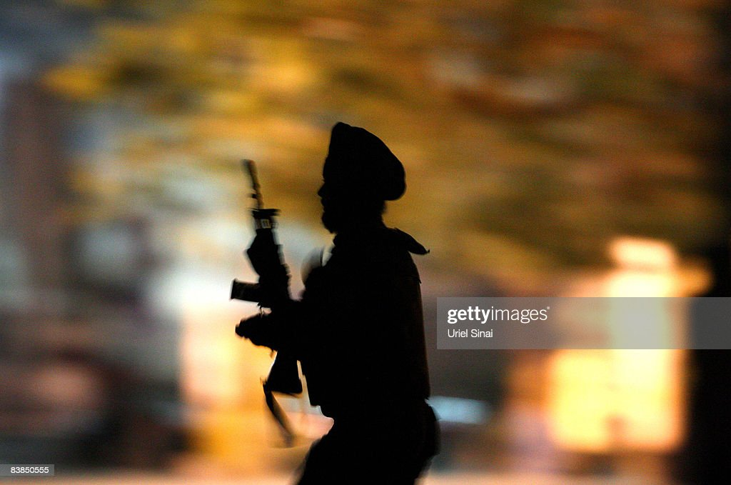 An Indian soldier runs for cover outside the Taj Mahal Palace Tower Hotel during an armed siege on November 28 2008 in Mumbai India The city of...