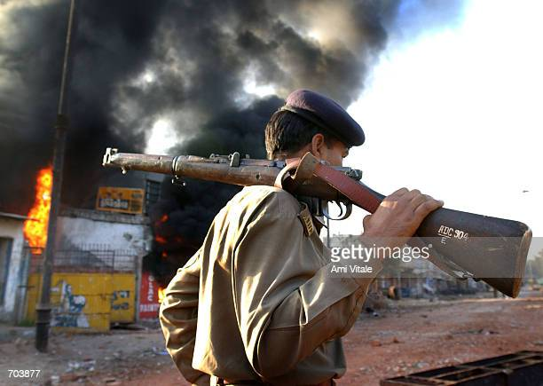 An Indian state police officer watches a Muslim owned shop burn March 1 2002 in Ahmadabad India two days after a Muslim mob attacked a train killing...