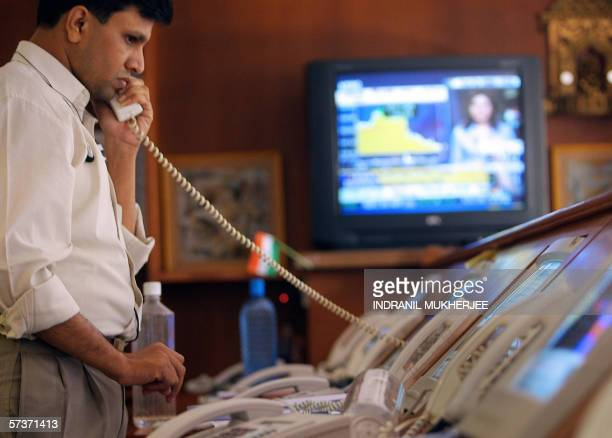 An Indian stock dealer at the Motilal Oswal Securities Limited monitors his screens as he takes an investor order over the phone as the Bombay Stock...