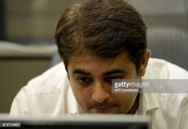 An Indian stockbroker trades shares on a terminal as the benchmark share index SENSEX crosses 32000 points at a brokerage house in Mumbai on July 13...