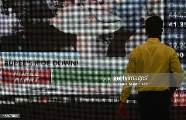 An Indian stockbroker watches currency rates on a screen during a trading session at the Bombay Stock Exchange in Mumbai on August 24 2015 The...