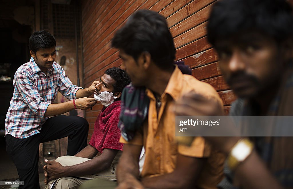 An Indian street barber shaves a customer as two men drink tea in the Old Quarters of New Delhi on May 12, 2013. The Indian government forecasts the economy will grow by at least six percent in this financial year, which began April 1, after estimated expansion of five percent last year - its slowest rate in a decade. AFP PHOTO/ Andrew Caballero-Reynolds