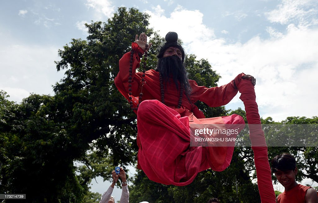 An Indian street charmer, dressed as Lord Shiva, performs a stunt as devotees of the International Society of Krishna Conciousness (ISKON) pull the holy rope of the Chariot of Lord Jagannath during the Rath Yatra celebration in Kolkata on July 10, 2013. According to mythology, the Ratha Yatra dates back some 5,000 years when Hindu god Krishna, along with his older brother Balaram and sister Subhadra, were pulled on a chariot from Kurukshetra to Vrindavana by Krishna's devotees. AFP PHOTO/Dibyangshu SARKAR