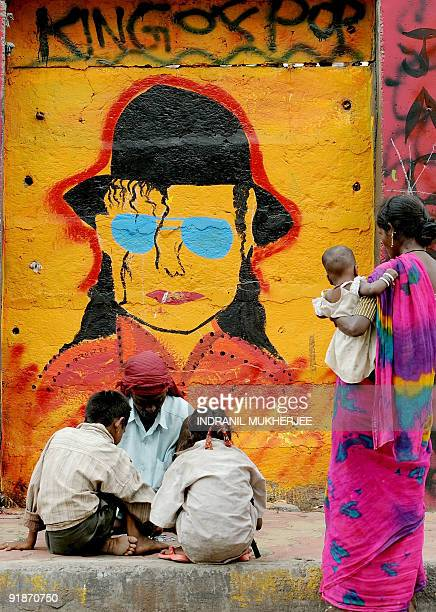 An Indian street dwelling mother watches her husband count loose change while sitting in front of a painting of the late 'King of Pop' Michael...