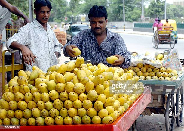 An Indian street vendor arranges a display of mangoes on a trolley as he waits for customers in New Delhi 20 July 2005 India is the world's largest...