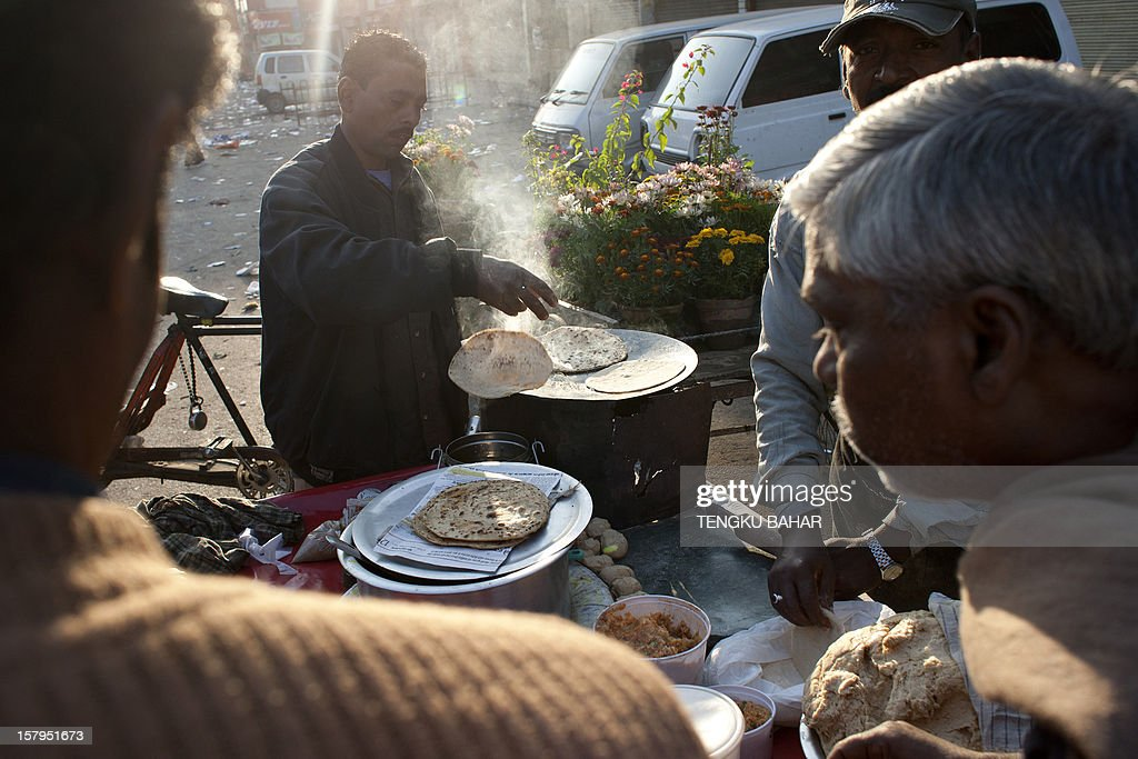 An Indian street vendor prepares flatbread as breakfast for customers at a retail market area in New Delhi on December 8, 2012. India has long been criticised as one Asia's most inefficient bureaucracies, with its byzantine regulations and widespread corruption seen as a major deterrent to foreign investment. AFP PHOTO/TENGKU BAHAR