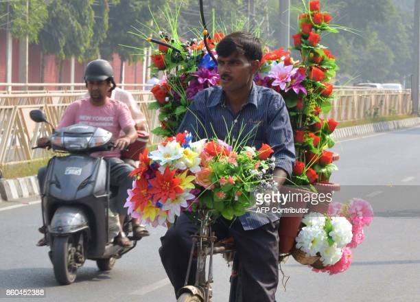 An Indian street vendor sells transport a load of artificial flowers on his bicycle in Amritsar on October 12 2017 / AFP PHOTO / NARINDER NANU