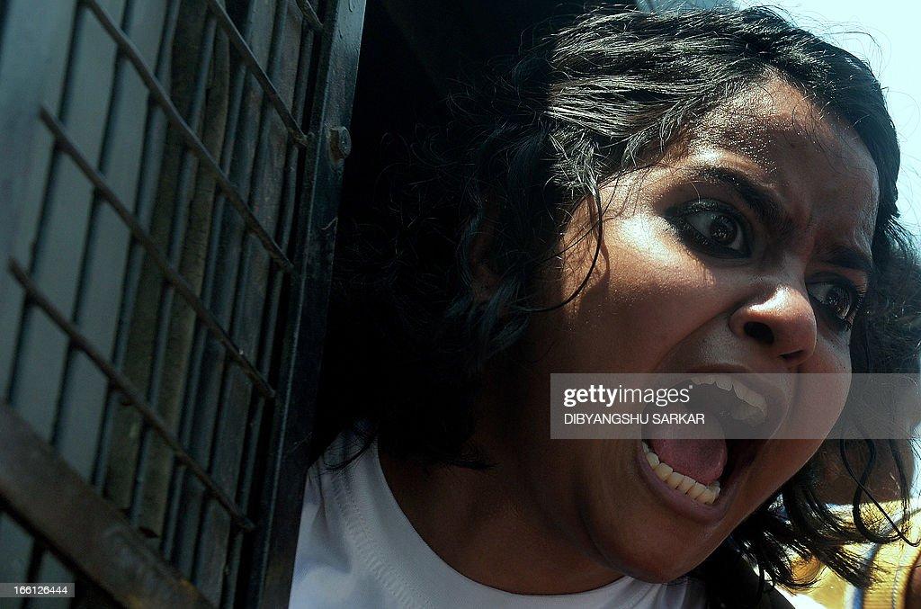 An Indian student from a leftist students' union shout slogans against Gujarat chief minister Narendra Modi from a police van outside the venue of Modi's meeting with business leaders in Kolkata on April 9, 2013. Police arrested students and other protesters and tightened the security around the venue. AFP PHOTO/Dibyangshu SARKAR