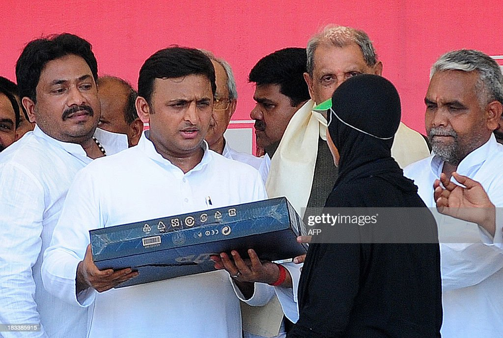 An Indian student receives laptop from the chief minister of Utar Pradesh, Akhilesh Yadav (2L), during a laptop distribution function in Allahabad on October 6, 2013. Yadav is a member of the socialist leaning Samajwadi Party.