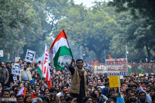 TOPSHOT An Indian student waves the Indian national flag at a protest against the arrest of an Indian student for sedition in New Delhi on February...