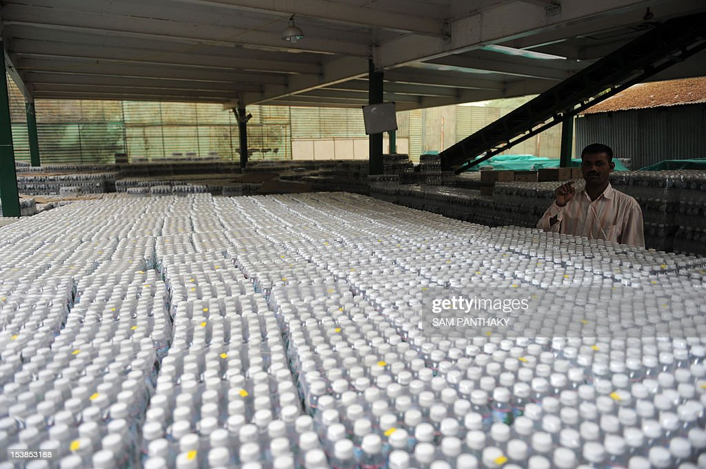 An Indian supervisor counts stocks at the Aava Natural Mineral Water plant in Ahmedabad on March 20 2012 ahead of World Water Day which falls on...