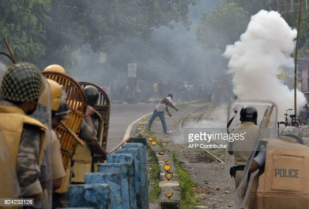 An Indian supporter of a separate Gorkhaland state throws a projectile at police during an indefinite strike at Sukna village in Darjeeling district...