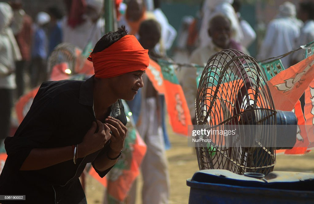 An indian supporter of Bhartiya janta party (BJP) cools off himself in front of a fan during national president of BJP Amit Shah's speech in Sardar Patel Kisan rally, in Allahabad on May 31,2016.