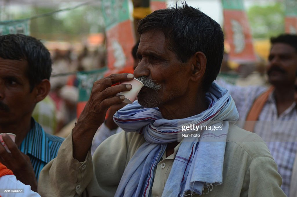 An indian supporter of Bhartiya janta party (BJP) takes tea during national president of BJP Amit Shah's speech in Sardar Patel Kisan rally, in Allahabad on May 31,2016.