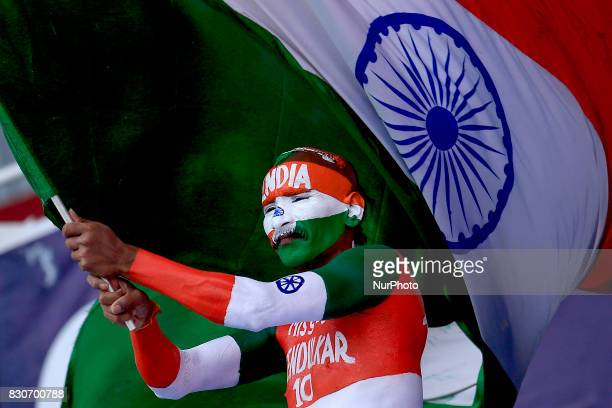 An Indian supporter waves the Indian national flag during the 1st Day's play in the 3rd Test match between Sri Lanka and India at the Pallekele...