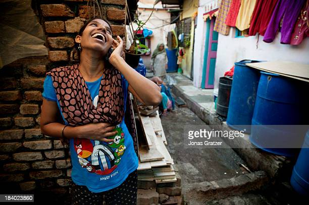 An Indian surrogate mother laughs as she talks on the phone in the alley of a Mumbai ghetto A clinic in Mumbai called 'Surrogacy India' have rented a...