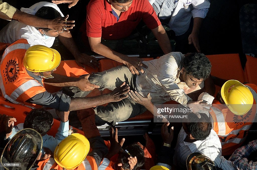 An Indian survivor reacts as National Disaster Relief Force (NDRF) members and firemen carry him away on a stretcher following his rescue from a collapsed building in Mumbai on March 14, 2014. An apartment block collapsed in the Indian financial hub Mumbai on March 14, killing one woman and injuring three other people in the latest in a series of deadly building cave-ins, authorities said. AFP PHOTO/ PUNIT PARANJPE
