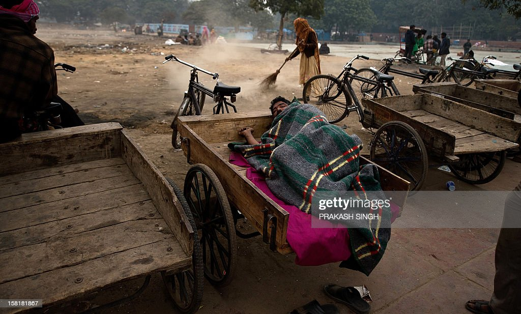 An Indian sweeper cleans the area as a tricycle rickshaw puller on his vehicle on a cold foggy morning in New Delhi on December 11, 2012. Winter temperatures in the Indian capital have dropped with rainy weather forecast over the next few days. AFP PHOTO/ Prakash SINGH