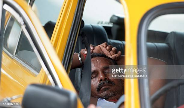 An Indian taxi driver rests in his parked car in Kolkata on May 25 2015 More than 430 people have died in two Indian states from a dayslong heatwave...