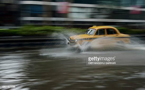 An Indian taxi drives along a waterlogged street following heavy rain in Kolkata on July 10 2015 AFP PHOTO/ Dibyangshu Sarkar