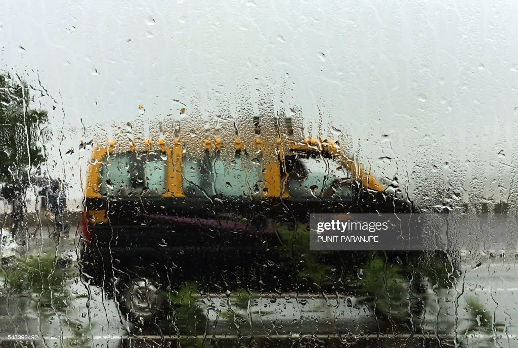An Indian taxi is driven in heavy rain showers in Mumbai on June 28, 2016. Annual monsoon rains have progressed to most parts of western and central India, easing fears of millions of desperate farmers after two straight years of drought, the weather department said. / AFP / PUNIT