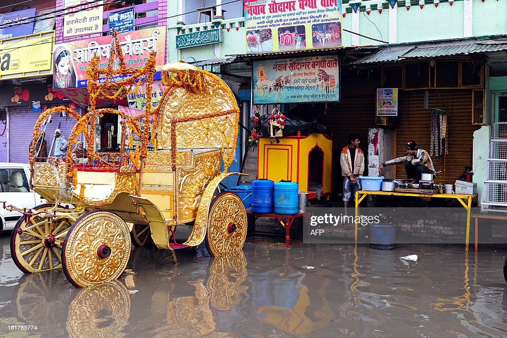 An Indian tea seller waits for customers beside a chariot parked in floodwaters following heavy rain in Allahabad on February 16, 2013. Moderate to heavy rains fell across northern India February 16, with night temperatures expected to drop in several areas across the region.