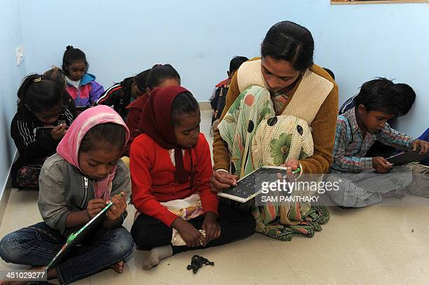 An Indian teacher assists underprivileged children during their lessons at Palodia village of Gandhinagar district some 25 kms from Ahmedabad on...
