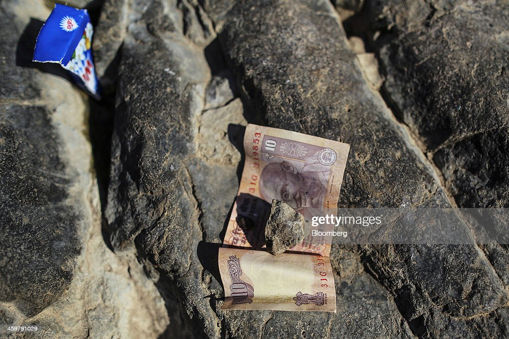 An Indian ten-rupee banknote sits on a rock beside a pond where a woman washes clothes, unseen, in Kainad, Maharashtra, India, on Saturday, Dec. 21, 2013. The construction of 600,000 kilometers (373,000 miles) of country roads, addition of 327 million rural phone connections and a rise in literacy to record levels since Prime Minister Manmohan Singh took office in 2004 has helped double the growth rate of Indias food output. Photographer: Dhiraj Singh/Bloomberg via Getty Images