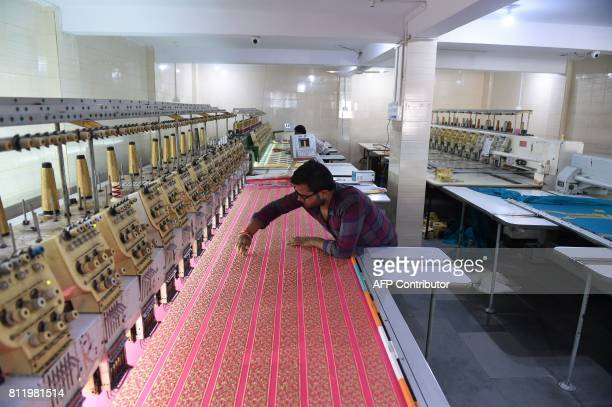 An Indian textile maker works on an embroidery machine at a workshop impacted by a cloth shortage due to protests over the recently introduced Goods...