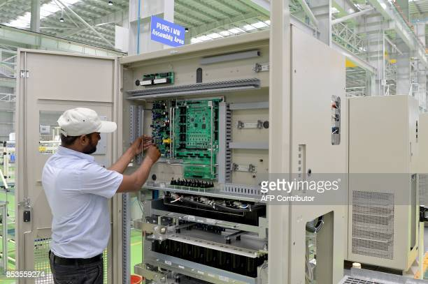 An Indian Toshiba MitsubishiElectric Industrial Systems Corporation worker conducts product checks in the assembly area of the power electronics...