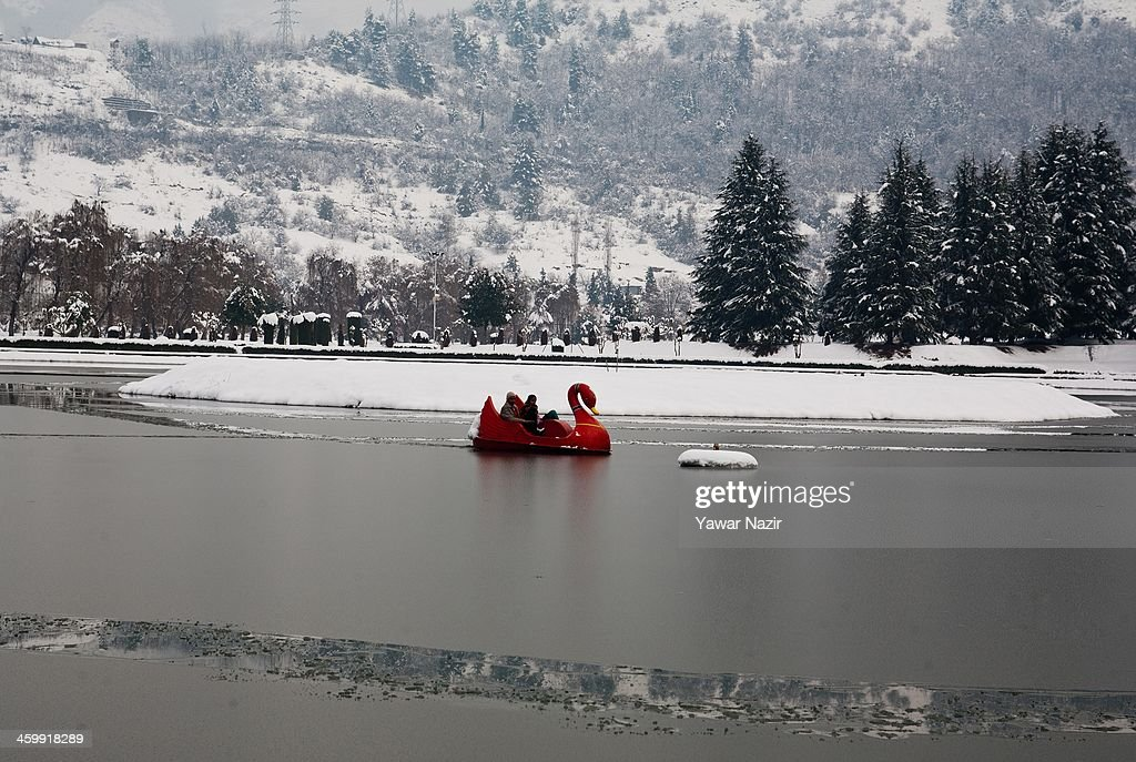 An Indian tourist couple takes a joy ride in an ice covered pond after snowfall on January 01, 2014 in Srinagar, the summer capital of Indian Administered Kashmir, India. Weather conditions have improved in Kashmir after a spell of heavy snowfall that had distrupted road and air traffic, cutting off the Valley from the rest of world .
