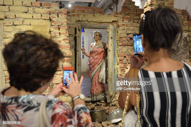 An Indian tourist poses for photos taken by friend next to a faux demolished wall recreating postPartition violence debris during the reinauguration...