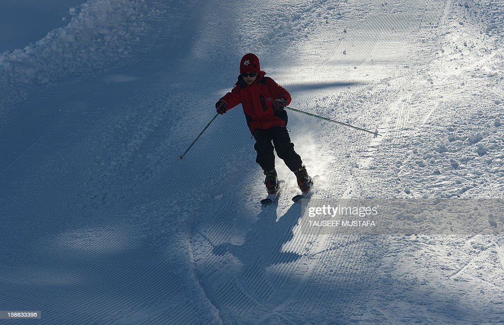 An Indian tourist skis down a slope in Gulmarg, about 55 kms north of Srinagar, on December 31, 2012. Gulmarg is the main ski destination in Indian Kashmir and hundreds of foreigners visit the slopes despite an ongoing insurgency in the region. AFP PHOTO/ Tauseef MUSTAFA