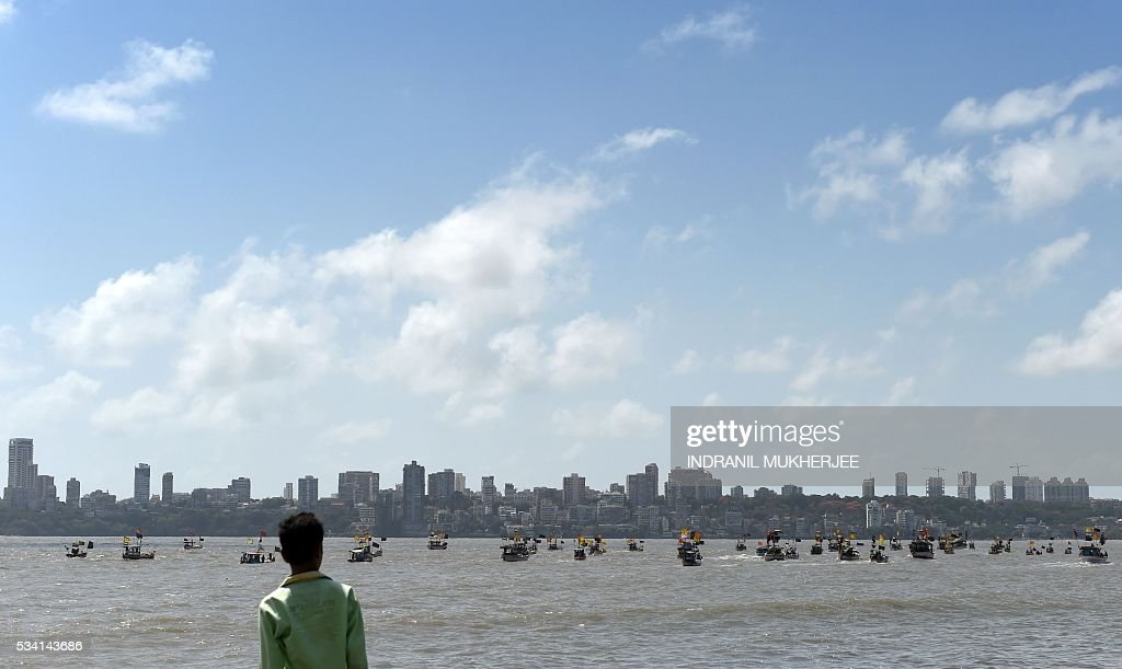 An Indian tourist watches fishing boats with black flags as they take part in a 'Sea-Rally' to protest against the construction of The Chhatrapati Shivaji Memorial in the Arabian Sea off the coast in Mumbai on May 25, 2016. Some 100 fishing boats and fishermen participated in this rally to highlight the conditions which are going to arise after the construction of the proposed sea memorial for the legendary warrior Shivaji which may cause adverse effects to the livelihood of fishermen. / AFP / INDRANIL