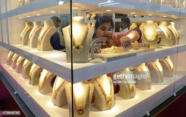 An Indian trader adjusts jewellry displayed during the Hyderabad Jewellery Pearl and Gem Fair in Hyderabad on June 5 2015 Over 150 exhibitors will...