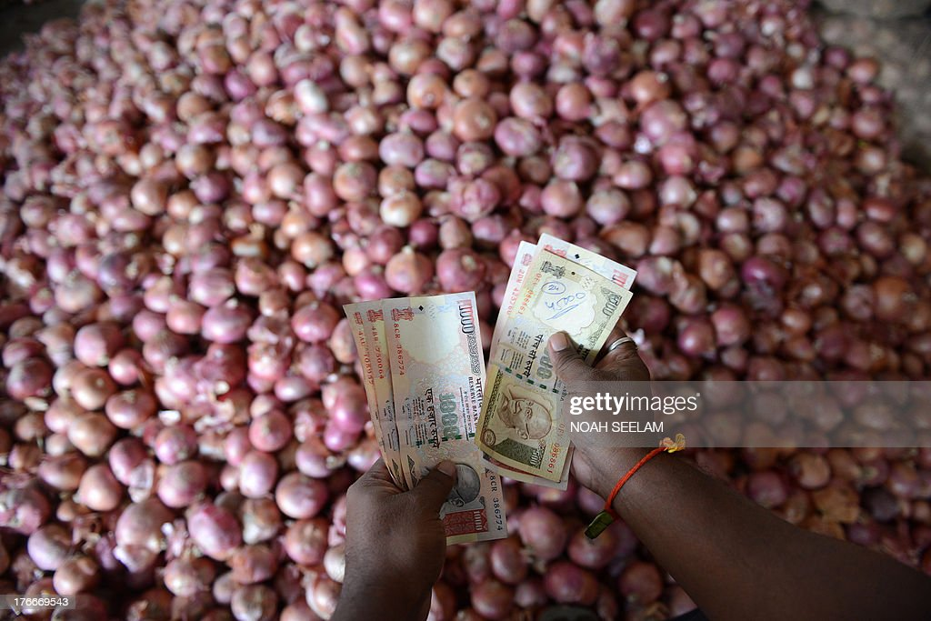 An Indian trader counts money as he deals in onions at a wholesale market yard in Hyderabad on August 17, 2013. India's food inflation rate rose to an annualized 9.5 percent led by a spike in onion prices which were up 34 percent from June. Onion prices have been rising in India as the crop has been hit by excessive rains. AFP PHOTO/Noah SEELAM