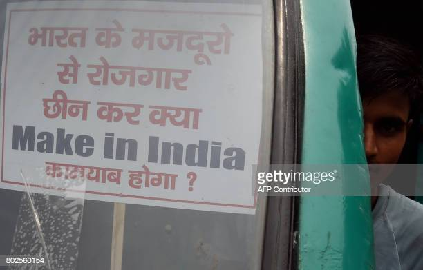 An Indian trader holds a 'Make in India' placard during a protest against the forthcoming Goods and Services Tax in New Delhi on June 28 2017 India...