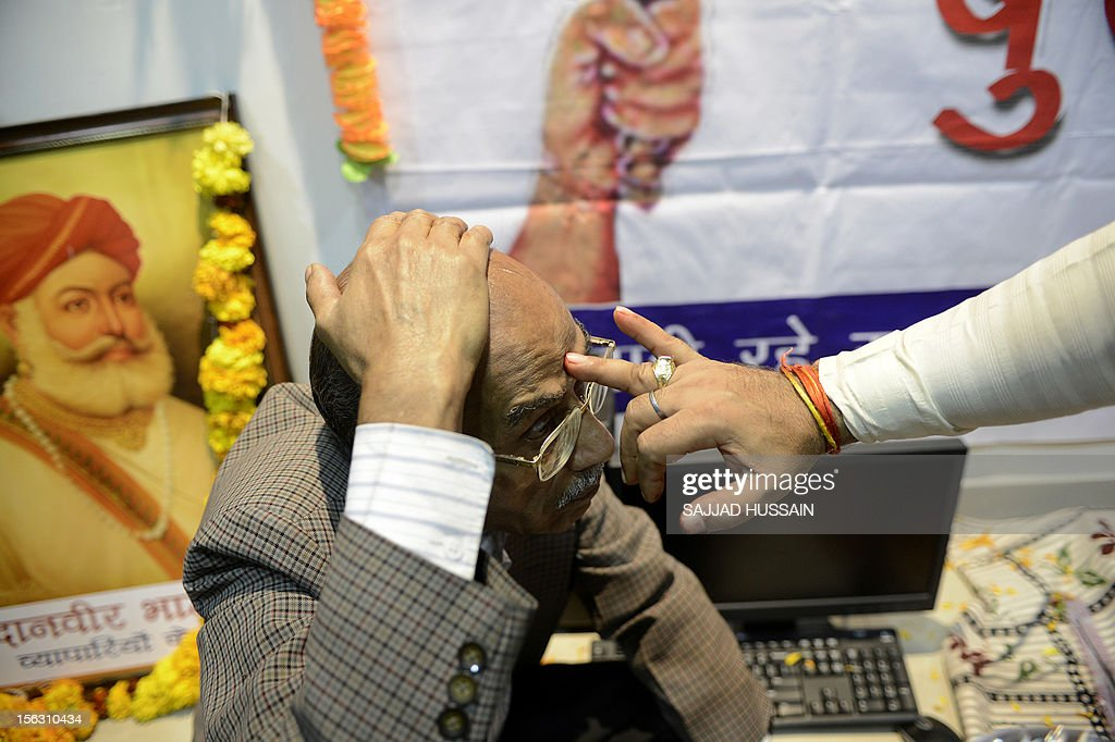 An Indian trader receives blessings during a ceremony in which traders worship electronic gadgets including iPads,laptops and mobile phones on Diwali, the Festival of Lights at their office in New Delhi on November 13, 2012. Since ages, the worshipping of account books has been an essential part of Diwali for the business community in India for prosperity of business. Signifying the modernisation of the retail trade in India, some traders are now including the worshipping of electronic gadgets. The festival of Diwali celebrates the victory of good over evil, light over darkness and knowledge over ignorance. AFP PHOTO/SAJJAD HUSSAIN