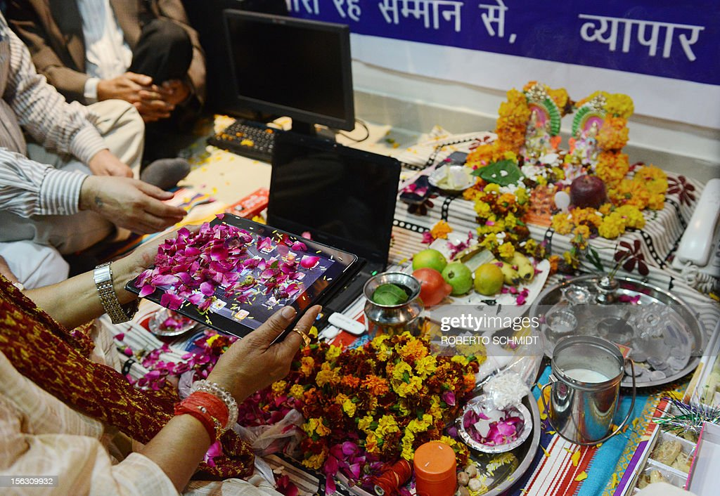 An Indian trader worships an iPad and electronic gadgets including laptops and mobile phones on Diwali, the Festival of Lights at the office in New Delhi on November 13, 2012. Since ages, the worshipping of account books has been an essential part of Diwali for the business community in India for prosperity of business. Signifying the modernisation of the retail trade in India, some traders are now including the worshipping of electronic gadgets. The festival of Diwali celebrates the victory of good over evil, light over darkness and knowledge over ignorance. AFP PHOTO/Roberto Schmidt
