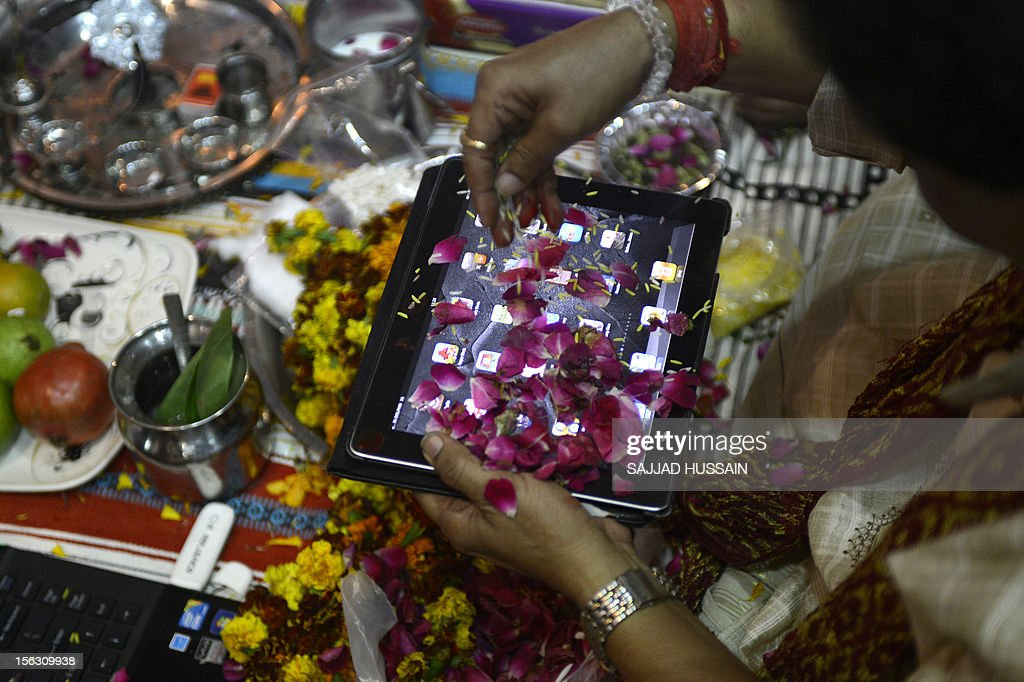 An Indian trader worships an iPad and electronic gadgets including laptops and mobile phones on Diwali, the Festival of Lights at the office in New Delhi on November 13, 2012. Since ages, the worshipping of account books has been an essential part of Diwali for the business community in India for prosperity of business. Signifying the modernisation of the retail trade in India, some traders are now including the worshipping of electronic gadgets. The festival of Diwali celebrates the victory of good over evil, light over darkness and knowledge over ignorance. AFP PHOTO/ SAJJAD HUSSAIN