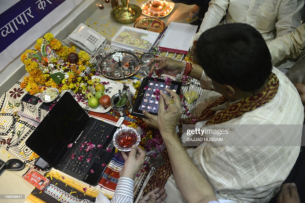An Indian trader worships an iPad and electronic gadgets including laptops and mobile phones on Diwali, the Festival of Lights at the office in New Delhi on November 13, 2012. Since ages, the worshipping of account books has been an essential part of Diwali for the business community in India for prosperity of business. Signifying the modernisation of the retail trade in India, some traders are now including the worshipping of electronic gadgets. The festival of Diwali celebrates the victory of good over evil, light over darkness and knowledge over ignorance.