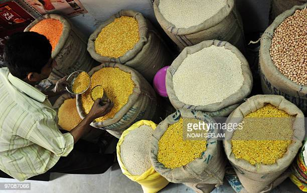 An Indian tradesman takes lentil samples at the wholesale market in Hyderabad on February 26 2010 as Finance Minister Pranab Mukherjee presents the...