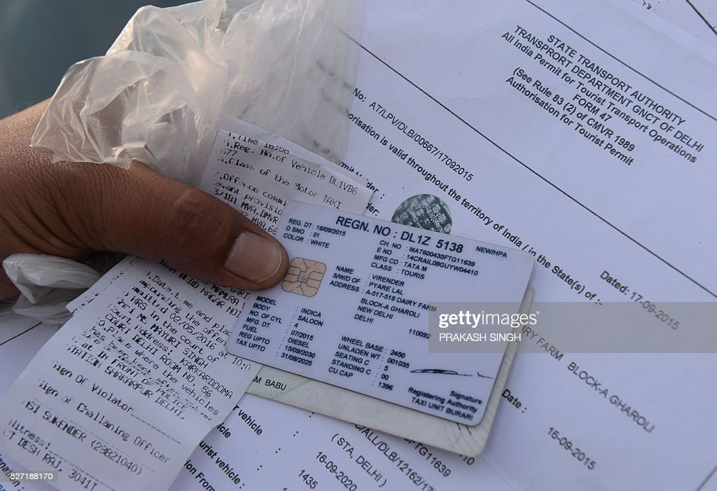 an Indian traffic police personnel checks the papers of the driver of a diesel taxi car in New Delhi on May 2, 2016. Hundreds of taxi drivers took to the streets of New Delhi to protest a court order banning diesel cabs from plying the roads of the world's most polluted capital. The ban would impact some 27,000 diesel taxis registered in Delhi, including app-based cab operators Ola and Uber. / AFP / PRAKASH