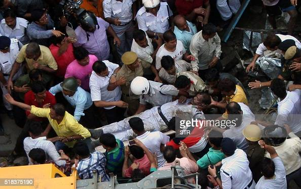 An Indian traffic policeman is carried by colleagues and volunteers after being rescued from underneath a collapsed flyover in Kolkata on March...